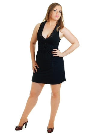 full-length portret van mooie plus size jonge blonde vrouw die zich voordeed op wit in zwarte jurk en pumps