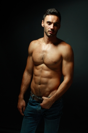 naked male body: portrait of topless athletic macho man posing over black background Stock Photo