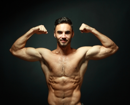 portrait of topless athletic macho man posing over black background photo