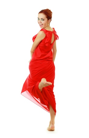 Young lady in red dress dancing barefoot on white background photo