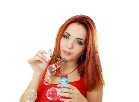 a beauty young redheared in red dress woman blowing soap bubbles Stock Photo - 14697191