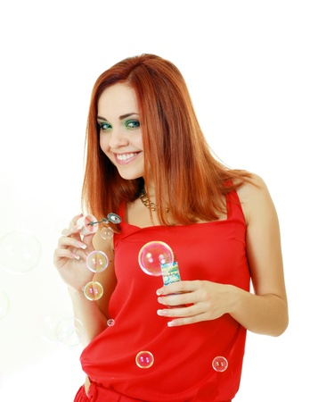 a beauty young redheared in red dress woman blowing soap bubbles Stock Photo - 14697189
