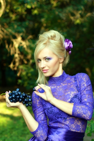 Beautiful Young Woman in violet dress with perfect make up eating grape and looking to the camera photo
