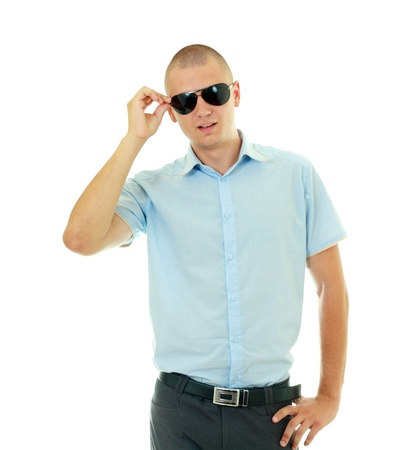 mistrustful bold young man taking off sunglasses isolated on white photo