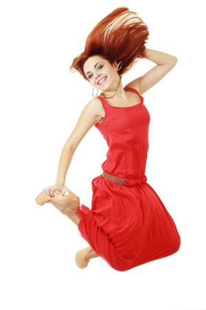 High-End Fashion Model with red hair red dress and heels jumping in studio on background photo