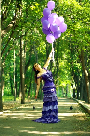 fashion beautiful young woman outdoors in the park with baloons in violet dress and violet baloons in her hand photo
