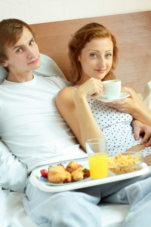 Relaxed young couple lying on bed comfortably with served breakfast in foreground photo