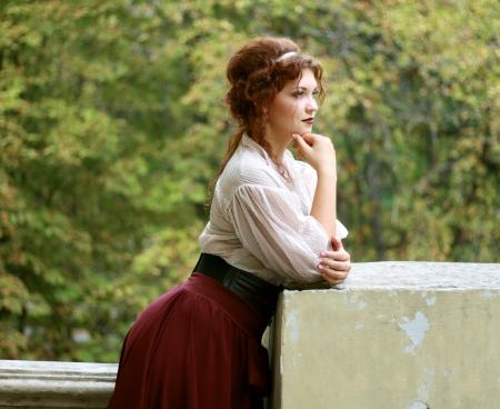 Doordachte jonge dame weared in oude mode jurk outdoor