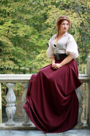 Doordachte jonge dame weared in oude mode jurk buiten zitten
