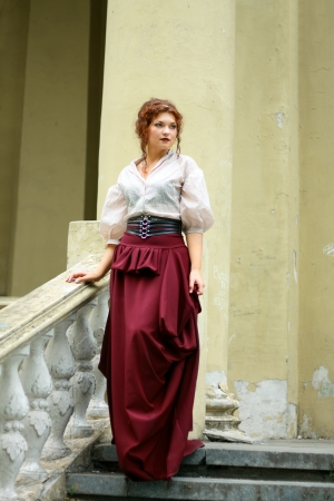 thoughtful Young lady weared in old fashion dress outdoor walking down stairs photo
