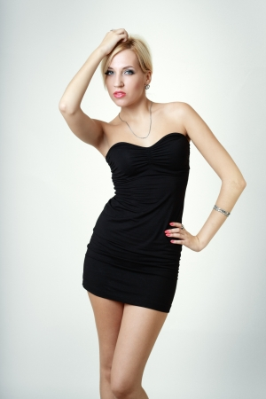 black dress: Young blond lady in black dress posing on light grey background