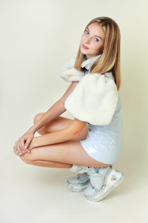 Portrait of trendy teen girl in miniskirt and leather dress sitting against white background photo