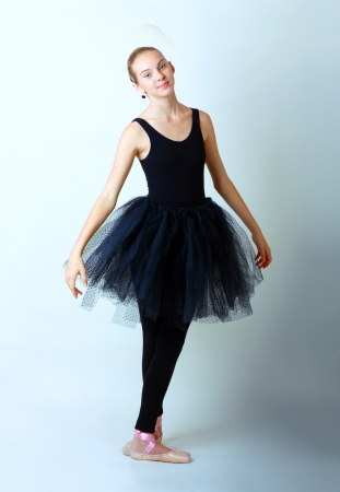 modern style dancer teen girl in black tutu posing on studio background photo