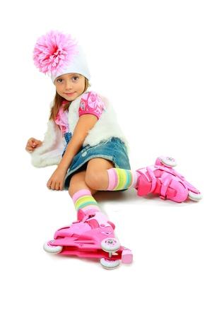 five years old: ragazza di cinque anni su pattini a rotelle rosa e cappello seduta sul pavimento