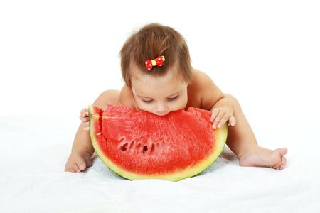 schattige kleine baby meisje eet watermeloen slice op witte achtergrond