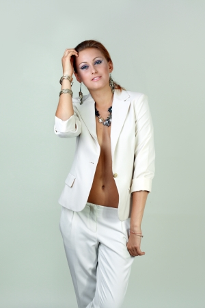 Beautiful woman wearing white suit standing over white wall