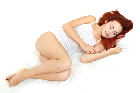 beautiful red head young woman sleeping over white background photo
