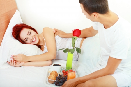 Man serves the breakfast  in bed  to his wife and awaking her. hight key light. focus on woman photo