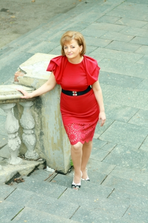 beautiful middleage woman in red dress walking up the stairs photo