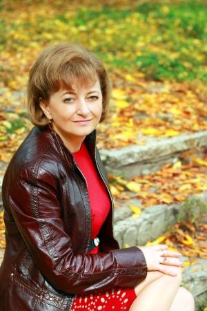 Schöne lächelnde Frau mittleren Alters im Freien im Park sitzen mit gelben Blättern im Hintergrund