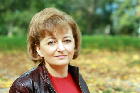 Beautiful smiling middle-aged woman outdoors in the park sitting with yellow leaves in background Stock fotó