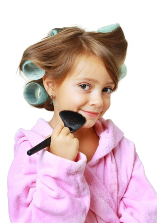 Beautiful girl with hair curlers putting on makeup, isolated on white photo