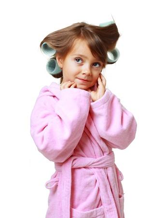 five years old: Cute Girl cinque anni con un pettine in bigodini su uno sfondo bianco in accappatoio rosa