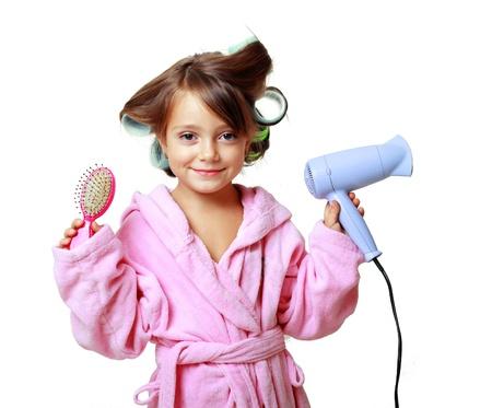 little models: linda ni�a de cinco a�os con un peine en bigud�es de pelo en un fondo blanco Foto de archivo