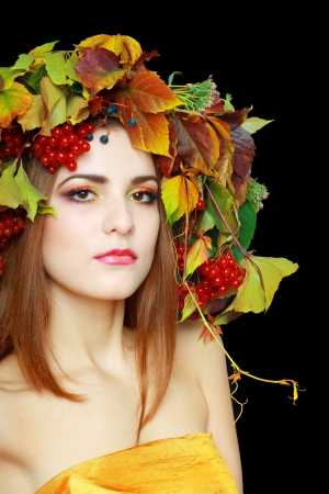 Autumn Woman in gold dress. Beautiful makeup isolated over black background. viburnum berries photo