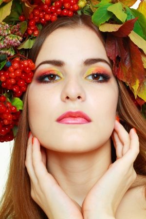 Autumn Woman close up. Beautiful makeup isolated over white background. viburnum berries photo
