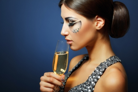 beautiful young woman with creative face art make up drinking Champagne Stock Photo - 17047812