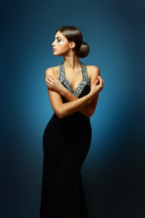 beautiful woman in sexy evening dress against dark background Stock Photo - 17047807