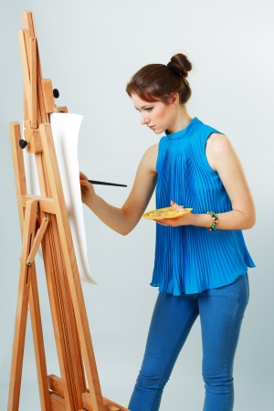 pastimes: young women painter with easel on light grey background