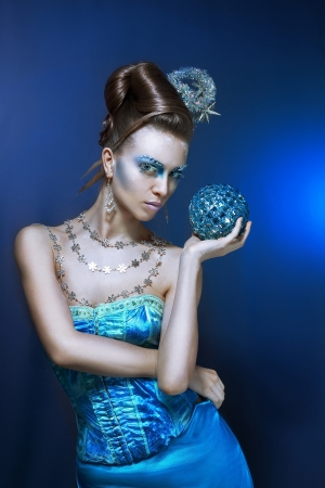 ce-queen. Young woman in creative image with silver artistic make-up. photo