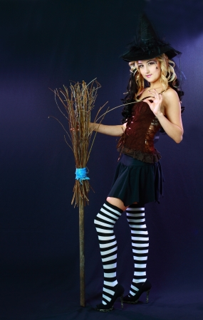 Sexy beautiful witch with broom on dark background Stock Photo - 17047816