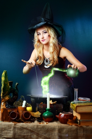 Sexy witch on a dark background making potion on wizard kitchen Stock Photo