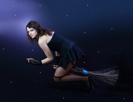 Sexy brunette witch flying on broom on a dark sky with stars Stock Photo - 17065064