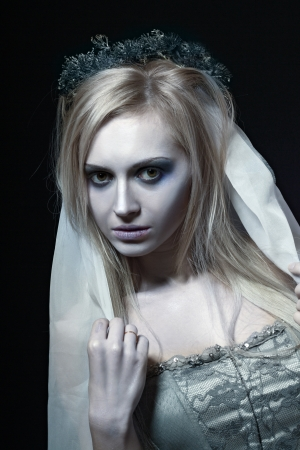 looked: Portrait of beautiful zombie corpse bride looked scary and standing at dark background. shot in studio