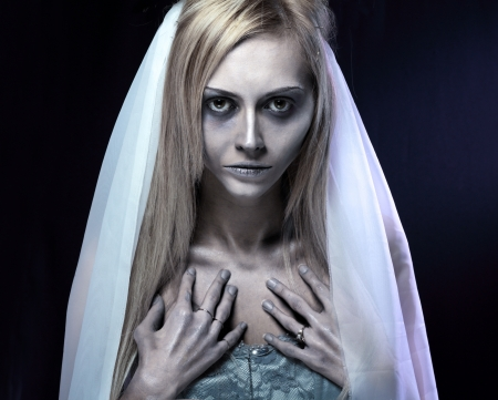 Portrait of beautiful zombie corpse bride looked scary and standing at dark background. shot in studio