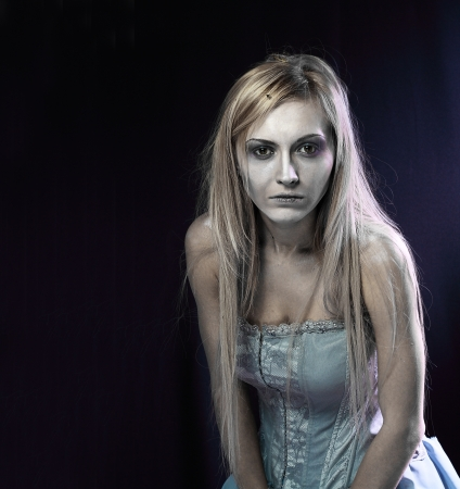 Portrait of beautiful zombie corpse bride looked scary and standing at dark background. shot in studio photo