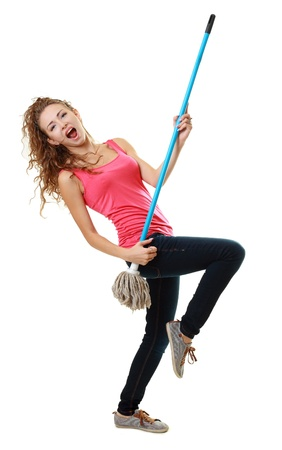 Beautiful woman having fun by playing air guitar with the mop. Isolated on white background.