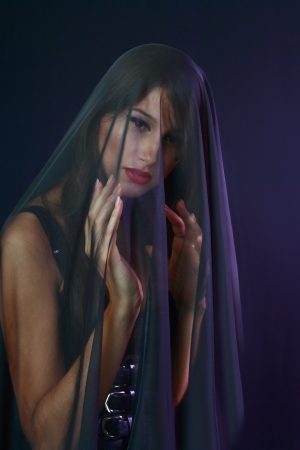 beautiful woman covered by transparent fabric on dark background Stock Photo - 17067652