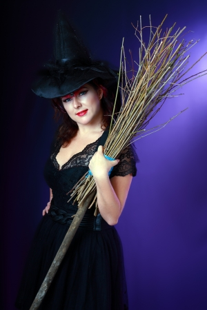 Sexy beautiful witch with broom on dark background Stock Photo - 17067621