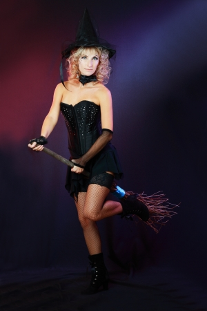 Sexy beautiful witch with broom on dark background Stock Photo - 17067745