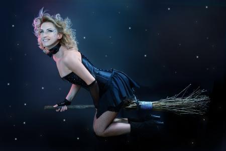 escoba: Sexy rubia bruja volando en la escoba en un cielo oscuro con estrellas Foto de archivo