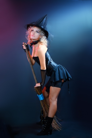 Sexy beautiful witch with broom on dark background Stock Photo - 17067437