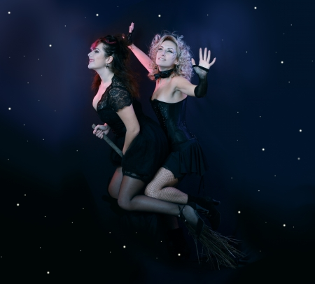 two halloween witches flying on broom on a dark sky with stars photo