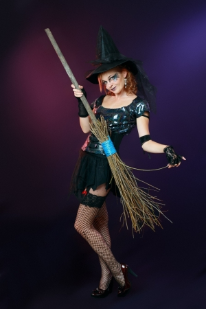 Sexy beautiful witch with broom on dark background Stock Photo - 17067645