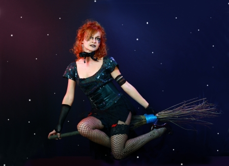 Sexy red haired witch flying on broom on a dark sky with stars photo