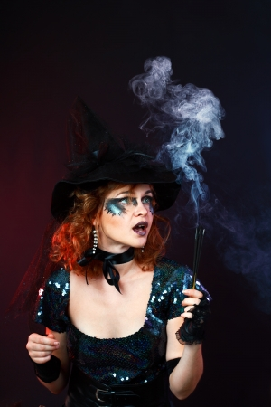Fantasy magic portrait of sexy beautiful woman with red hair and witch hat photo